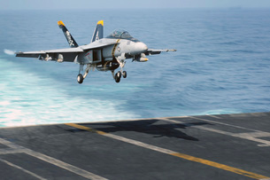 An F/A-18F Super Hornet prepares to land on the flight deck USS Dwight D. Eisenhower.の写真素材 [FYI02694558]