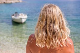 Blonde woman looking at boat in oceanの写真素材 [FYI02694570]