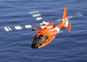 A Coast Guard HH-65A Dolphin rescue helicopter in flight.の写真素材 [FYI02694618]