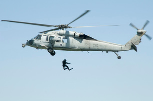 A diver is lowered from an SH-60B Seahawk helicopter.の写真素材 [FYI02694717]