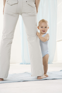 Baby holding on to mother's pantsの写真素材 [FYI02694747]