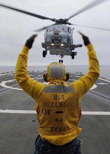 Petty Officer guides an SH-60R Sea Hawk helicopter onto the flight deck of USS McClusky.の写真素材 [FYI02694857]