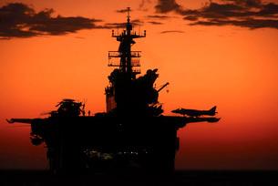 The setting sun silhouettes the amphibious assault ship USSの写真素材 [FYI02694900]