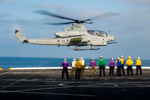 Sailors and Marines watch an AH-1Z Viper attack helicopter lift off the flight deck of USS New Orleaの写真素材 [FYI02695099]
