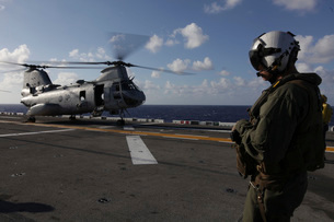 A crew chief watches a CH-46E Sea Knight helicopter aboard USS Makin Island.の写真素材 [FYI02695201]
