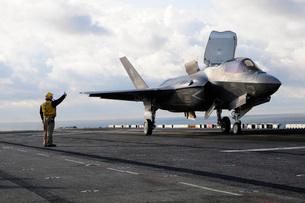 Aviation Boatswain's Mate signals the pilot to lift an F-35B Lightning II off the flight deck.の写真素材 [FYI02695228]