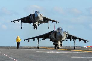 An AV-8B Harrier prepares for takeoff as another lands aboarの写真素材 [FYI02695281]