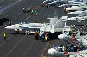 Sailors push an F/A-18C Hornet in preparation for flight operations.の写真素材 [FYI02695329]