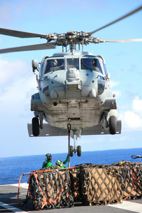 An HH-60H Sea Hawk helicopter picks up supplies from the flight deck.の写真素材 [FYI02695342]