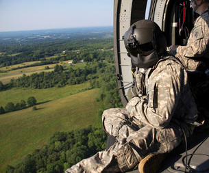An Army crew chief looks out the door of a UH-60 Black Hawkの写真素材 [FYI02695354]