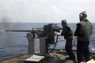 Gunner fires a Mark 38 machine gun aboard USS Frank Cable.の写真素材 [FYI02695406]