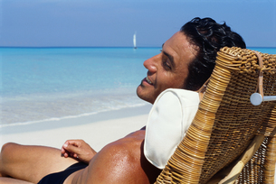 Man relaxing in a wicker chair on the beach, Cubaの写真素材 [FYI02695436]
