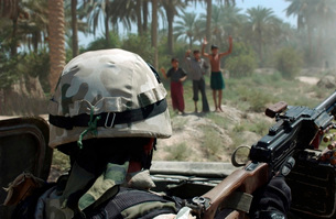 Local Iraqi children wave to a Polish Army Soldier manning aの写真素材 [FYI02695717]
