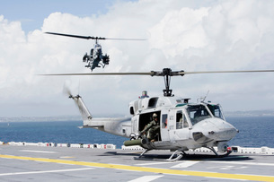 A UH-1N Huey and an AH-1W Super Cobra land on flight deck of USS Essex.の写真素材 [FYI02695813]