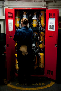 Fireman stows a self-contained breathing apparatus in a locker.の写真素材 [FYI02695935]
