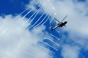 An HH-60H Sea Hawk helicopter releases countermeasure flares.の写真素材 [FYI02696086]