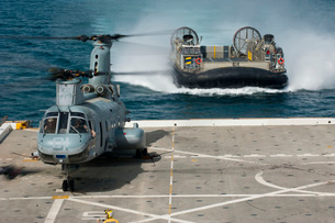 A hovercraft approaches USS New Orleans as a CH-46E Sea Knight sits on the flight deck.の写真素材 [FYI02696133]