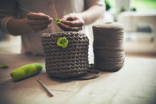 Midsection of woman knitting woolen purse at homeの写真素材 [FYI02696177]