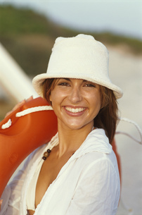 Young woman in sun hat carrying life preserverの写真素材 [FYI02696253]