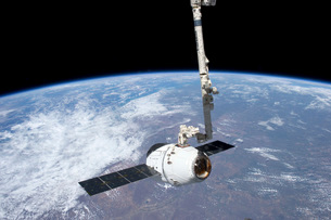 The SpaceX Dragon cargo craft in the grasp of the Canadarm2.の写真素材 [FYI02696394]