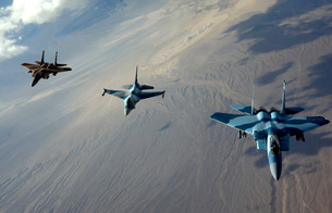 F-15 Eagles and a F-16 Fighting Falcon fly in formation.の写真素材 [FYI02696468]