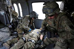 U.S. Army flight medics aid a simulated casulaty in a UH-60 Black Hawk.の写真素材 [FYI02696479]