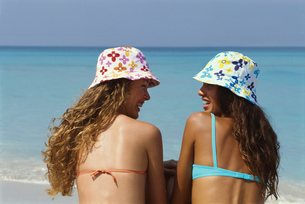 Rearview, two young women sitting on the beach in bikinis and floral beach Cubaの写真素材 [FYI02696526]