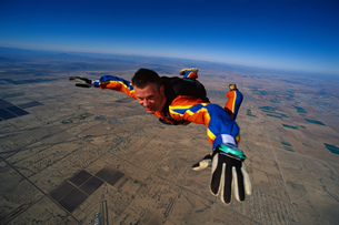 Close-up of skydiving man in colourful costume in mid-airの写真素材 [FYI02696543]