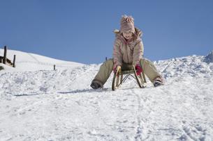 Child riding on sled, Luesener Alm, Dolomite Alps, South Tyrol, Italyの写真素材 [FYI02696581]