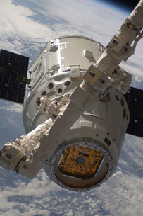 The SpaceX Dragon commercial cargo craft during grappling operations with Canadarm2.の写真素材 [FYI02696587]