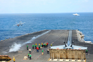 Two F/A-18 Hornets take off from the aircraft carrier USS Ronald Reagan.の写真素材 [FYI02696620]