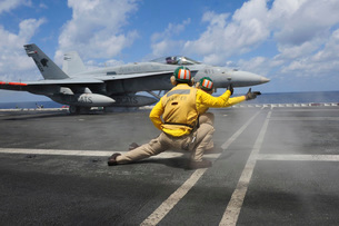 Shooters give the signal to launch an F/A-18C Hornet.の写真素材 [FYI02696627]