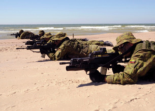 Lithuanian Special Forces members lie in formation on a beacの写真素材 [FYI02696633]