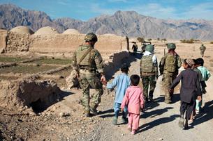 hildren walk alongside coalition force members in Afghanistan.の写真素材 [FYI02696678]