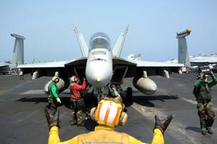 An aircraft director signals to the pilot of an F/A-18F Super Hornet.の写真素材 [FYI02696759]