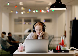 Businesswoman listening music while working late on laptop in creative officeの写真素材 [FYI02696983]