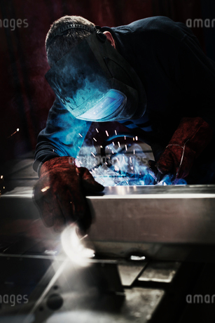 Welder using welding torch in steel factoryの写真素材 [FYI02697010]