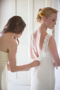 Bridesmaid helping bride with dressing in domestic roomの写真素材 [FYI02697029]