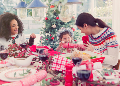 Mother and daughter pulling Christmas cracker at dinnerの写真素材 [FYI02697041]