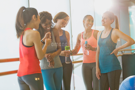 Smiling women talking and drinking water in sunny gym studioの写真素材 [FYI02697052]