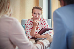Therapist listening to couple in couples therapy counseling sessionの写真素材 [FYI02697090]