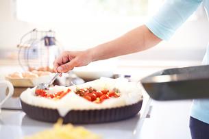 Woman preparing tomato quiche in kitchenの写真素材 [FYI02697091]