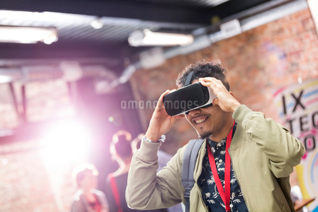 Man trying virtual reality simulator glasses at technology conferenceの写真素材 [FYI02697092]