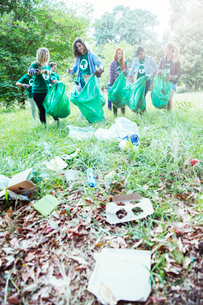 Environmentalist volunteers picking up trash in fieldの写真素材 [FYI02697102]