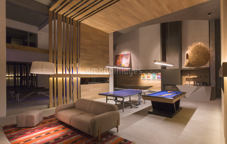 Illuminated pool table and ping pong table in modern, luxury home showcase interior game roomの写真素材 [FYI02697165]