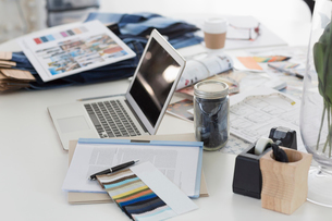 Laptop, swatches, proofs and paperwork on desk in fashion desk officeの写真素材 [FYI02697191]