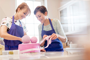 Female caterers finishing pink wedding cake in kitchenの写真素材 [FYI02697210]