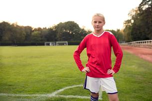 Portrait of confident girl standing on soccer fieldの写真素材 [FYI02697246]