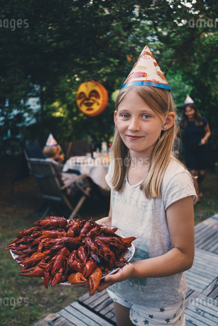 Portrait of girl holding plate of crayfish at garden dinner partyの写真素材 [FYI02697257]