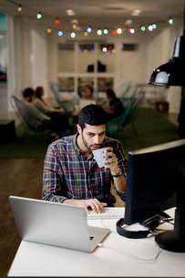 Businessman having coffee while working late in creative officeの写真素材 [FYI02697270]